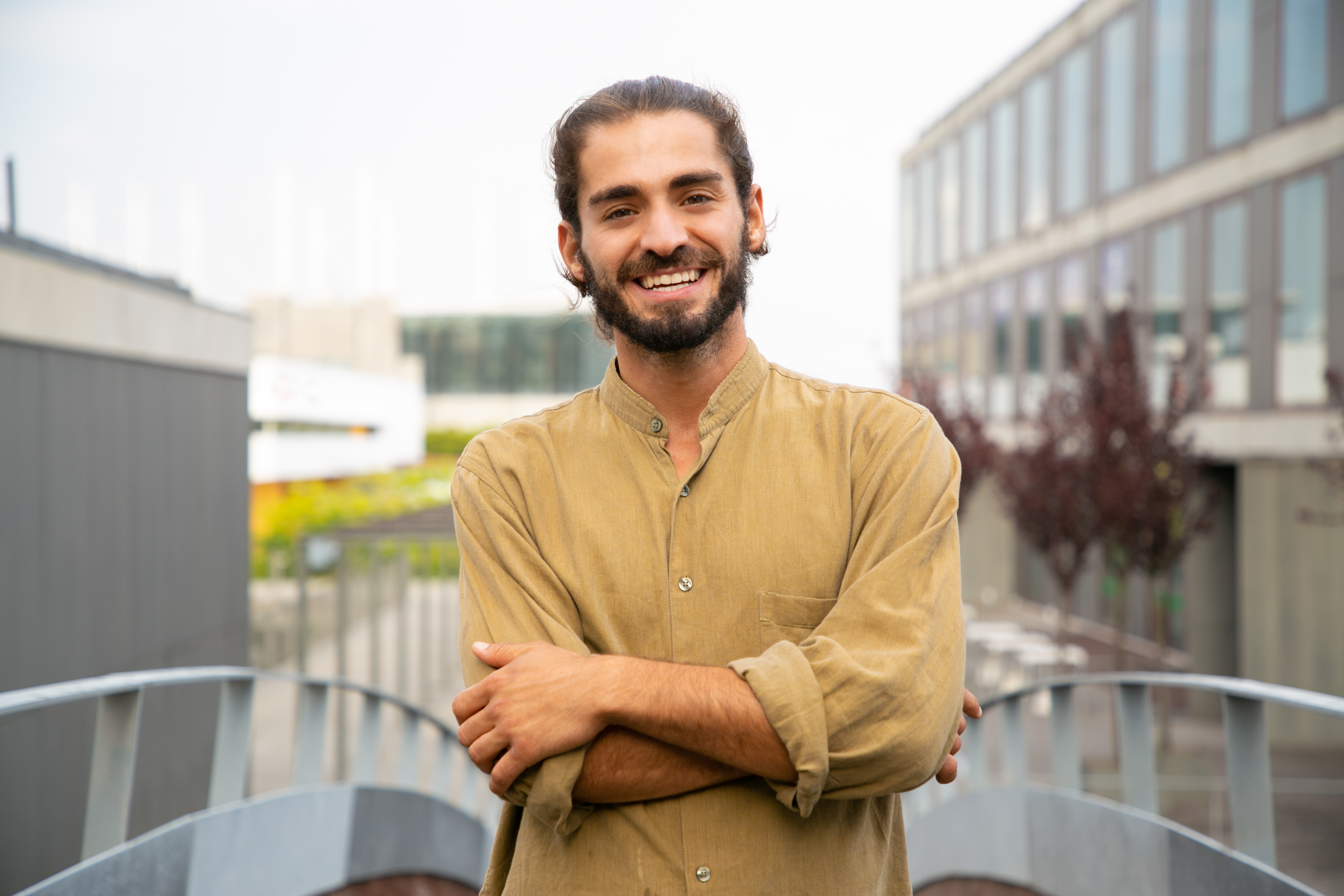 Happy joyful hipster guy posing for camera outside. Young man in casual with bun and stubble standing in urban settings, looking at camera and smiling. Male portrait concept
